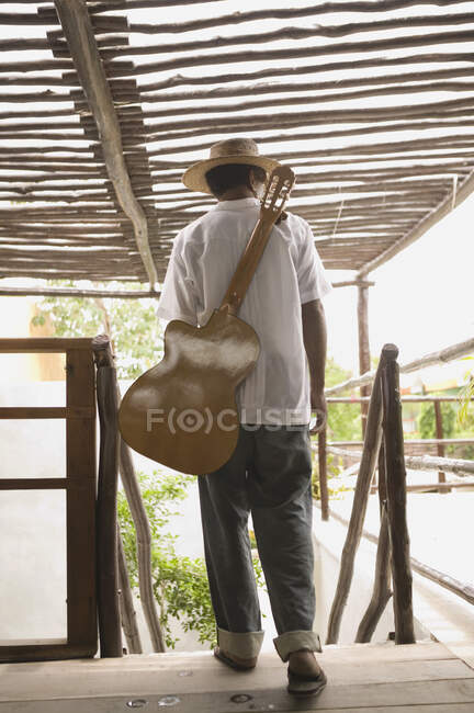 Full rear view of man with guitar on back — Stock Photo