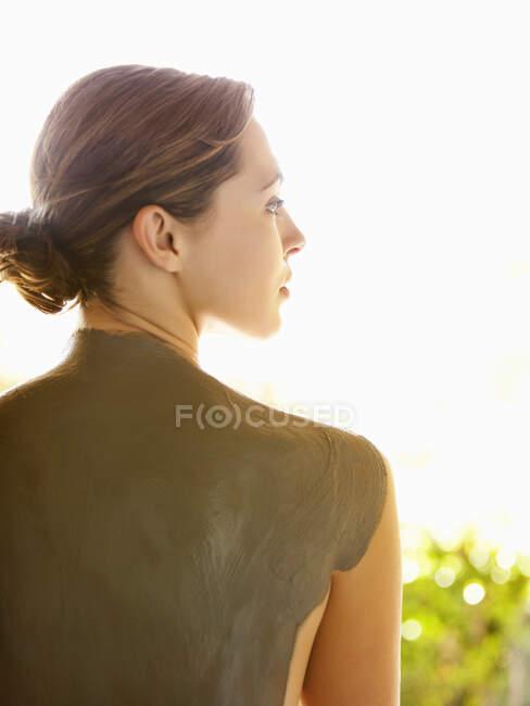 Белая женщина с грязью на спине — стоковое фото