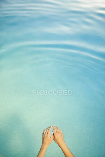 Woman swimming in swimming pool, overhead view, arms and hands. — Stock Photo
