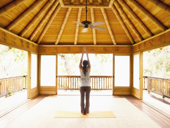 Задний вид женщины, стоящей с поднятыми руками внутри йоги и пагоды медитации на роскошном курорте — стоковое фото