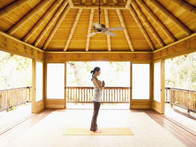 Профиль женщины, стоящей в молитвенном положении внутри йоги и пагоды медитации на роскошном курорте — стоковое фото