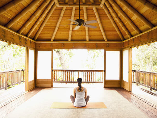 Rear view of woman sitting in lotus position on floor of yoga and meditation pagoda at a luxury resort — Stock Photo