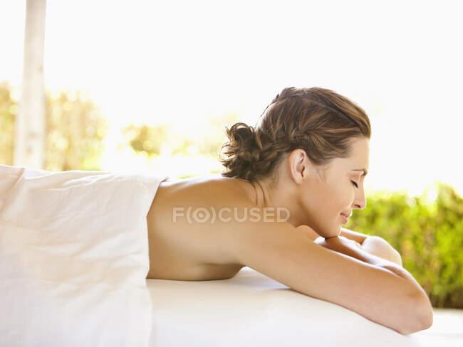 Усміхнена жінка з закритими очима лежала на масажному столі в розкішному курорті в долині Напа, Каліфорнія. — стокове фото