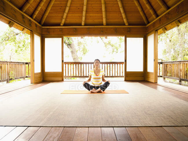 Женщина, сидящая в позе лотоса на полу йоги и пагоды медитации на роскошном курорте — стоковое фото