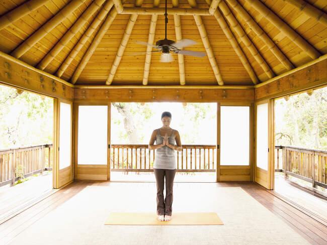 Женщина, стоящая в молитвенном положении внутри йоги и пагоды медитации на роскошном курорте — стоковое фото