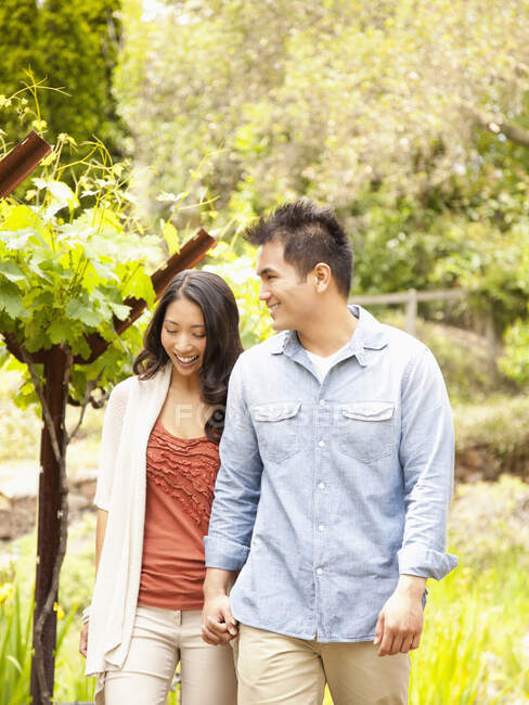 Chinesisches Paar hält Händchen beim Gang durch das Weinland im kalifornischen Napa Valley — Stockfoto