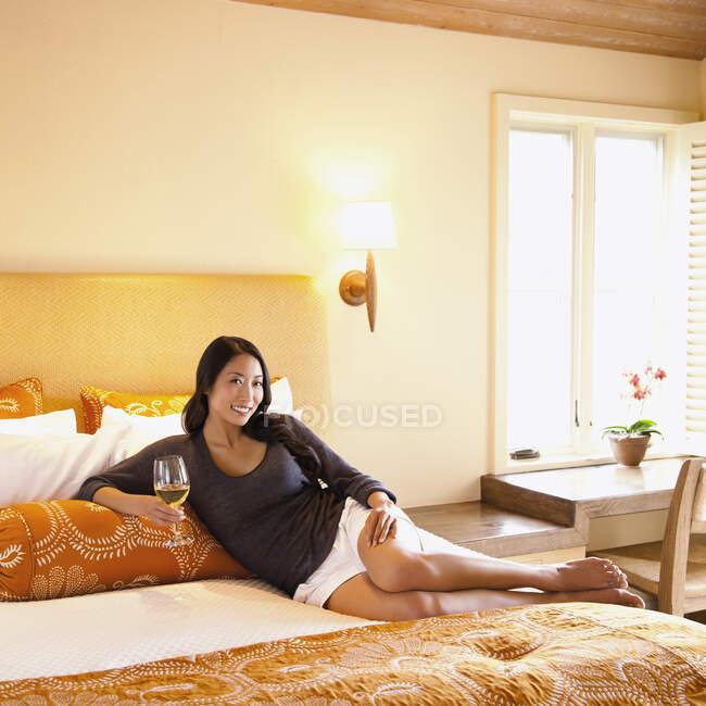 Mujer acostada en la cama de la habitación de hotel de lujo bebiendo vino en Napa Valley, California - foto de stock