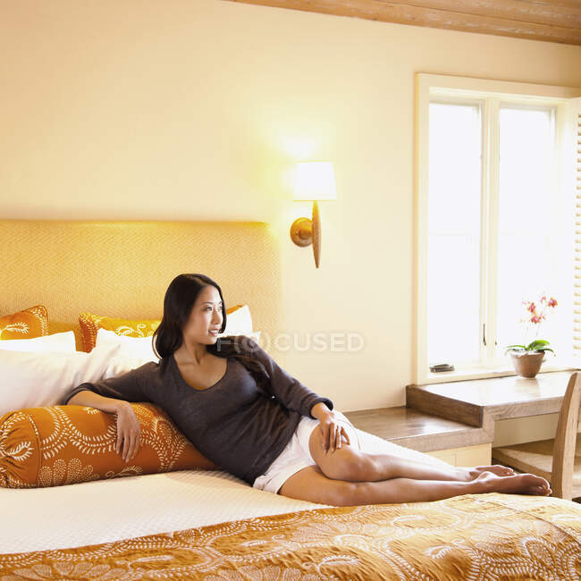 Mujer acostada en la cama de la habitación de hotel del complejo de lujo mirando hacia fuera en Napa Valley, California - foto de stock