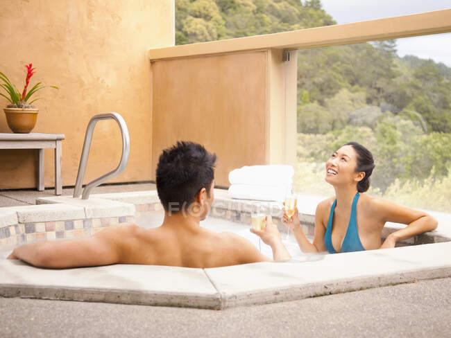 Cinese coppia rilassante in vasca idromassaggio a lusso spa bere champagne con vista paese del vino — Foto stock