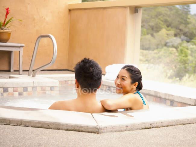 Cinese coppia relax in vasca idromassaggio presso spa di lusso con vista paese del vino in California — Foto stock