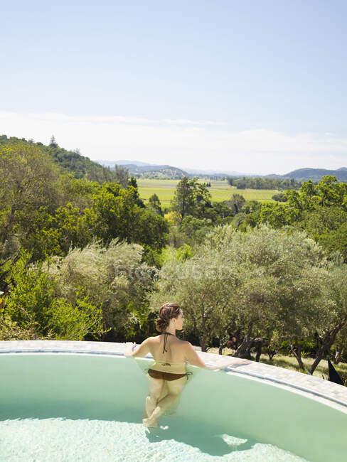Donna in piedi con le braccia distese sul bordo della piscina a sfioro in un resort di lusso con vista sul paese del vino a Napa Valley, California — Foto stock