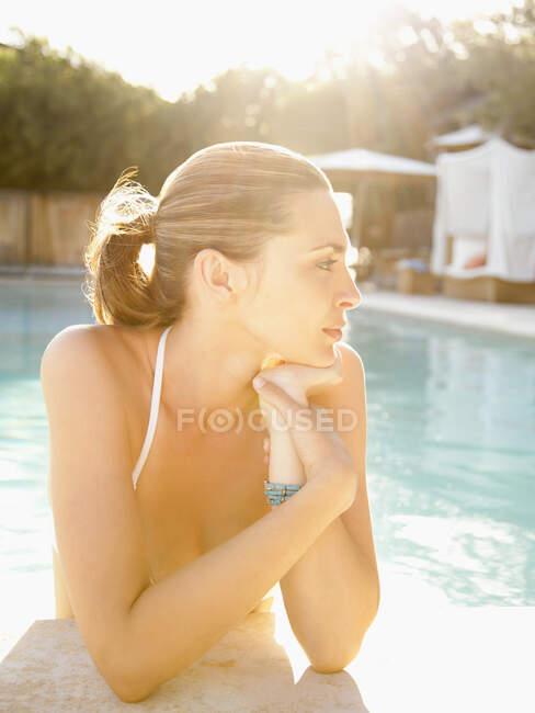 Schöne beschauliche Frau im Wasser, die sich an den Rand des Swimmingpools eines kalifornischen Luxus-Resorts lehnt — Stockfoto