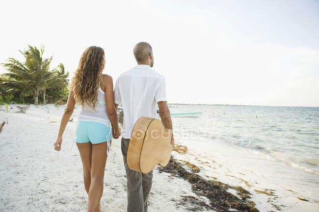 Jeune couple marchant sur la plage — Photo de stock