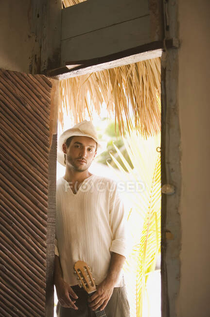 Молодой человек стоит в дверях с гитарой и смотрит в камеру — стоковое фото