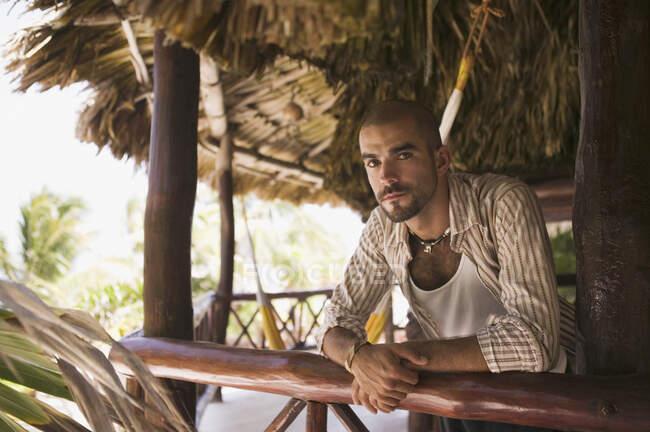 Jeune homme penché sur un poteau dans une cabane de paille — Photo de stock