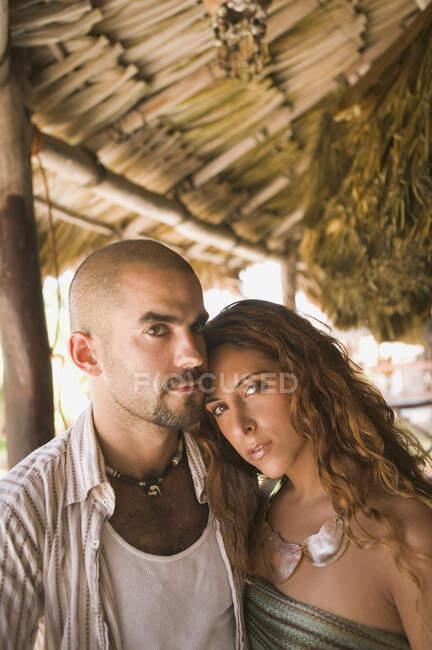 Jeune couple étreignant dans une cabane de paille — Photo de stock