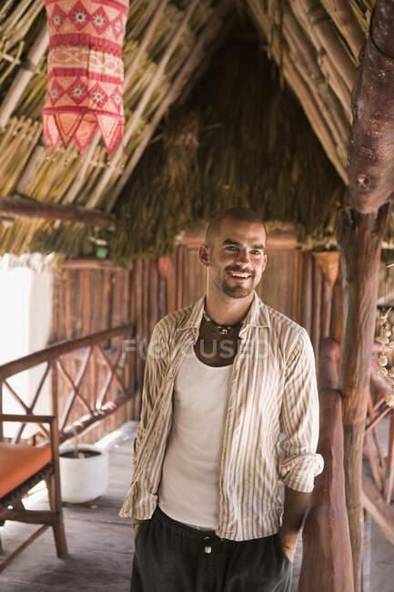 Jeune homme souriant dans une cabane de paille — Photo de stock