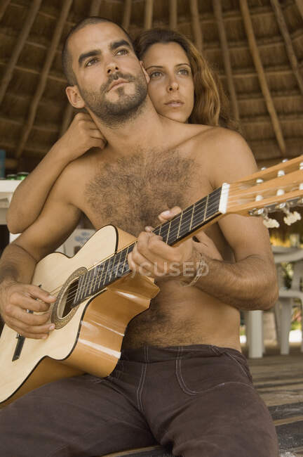 Young man playing guitar and his girlfriend hugging him — Stock Photo