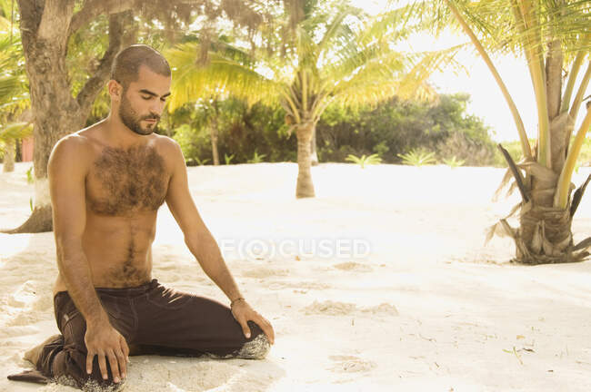 Young man kneeling in the sand meditating — Stock Photo