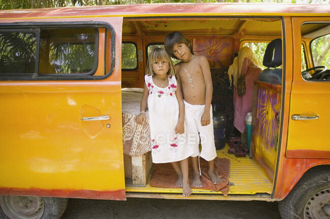 Children posing for the camera inside van — Stock Photo