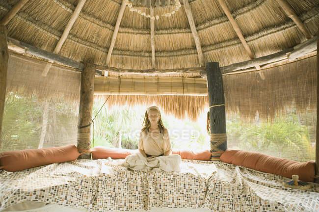 Молодая женщина медитирует на кровати в хижине — стоковое фото