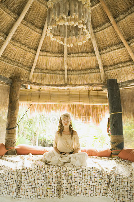 Young woman meditating on bed in hut — Stock Photo
