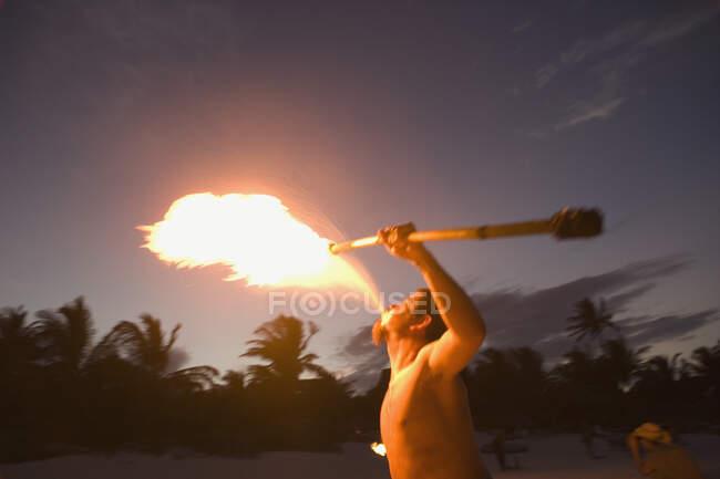 Человек выполняет и дышит огнем — стоковое фото