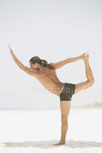Junger Mann macht Yoga am Strand — Stockfoto