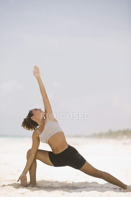 Young woman stretching on the beach — Stock Photo