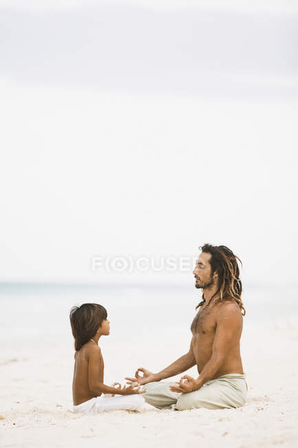 Father and son meditating on the beach — Stock Photo