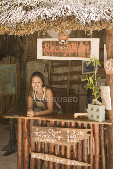 Jeune femme travaillant à la réception d'une plage — Photo de stock