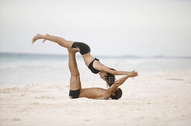 Couple practicing gymnastics on the beach — Stock Photo