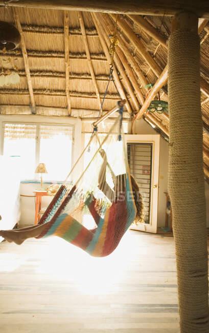 Jeune femme assise dans un hamac à l'intérieur — Photo de stock