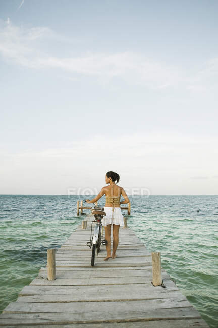 Young woman walking with bike on pier, back view — Stock Photo