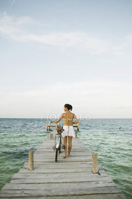 Jeune femme marchant à vélo sur jetée, vue arrière — Photo de stock