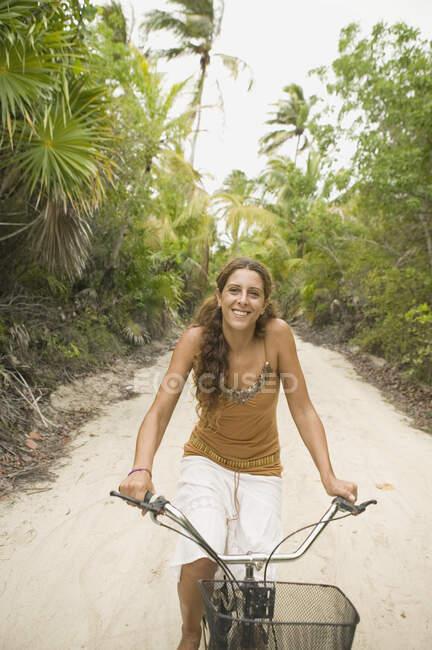 Jeune femme en vélo sur un chemin sablonneux — Photo de stock