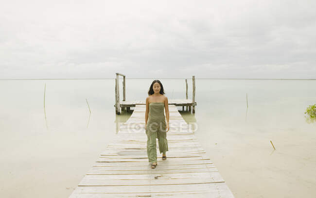 Woman walking down wooden pier, full length, front view — Stock Photo