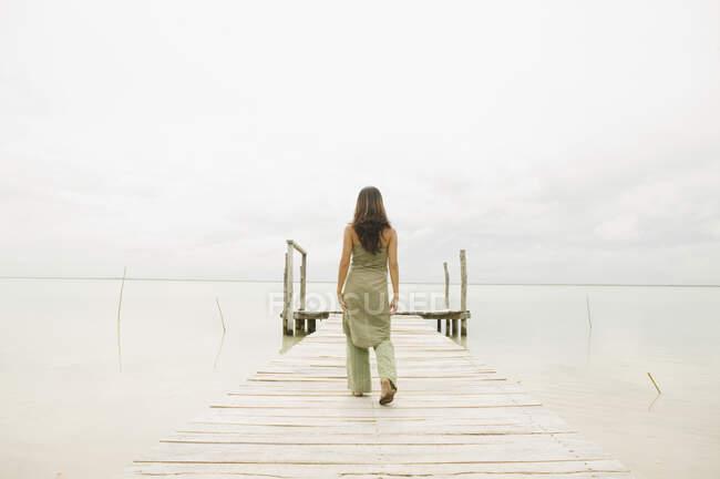 Woman walking down pier, back view — Stock Photo