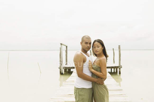 Paar umarmt sich auf einer Seebrücke — Stockfoto