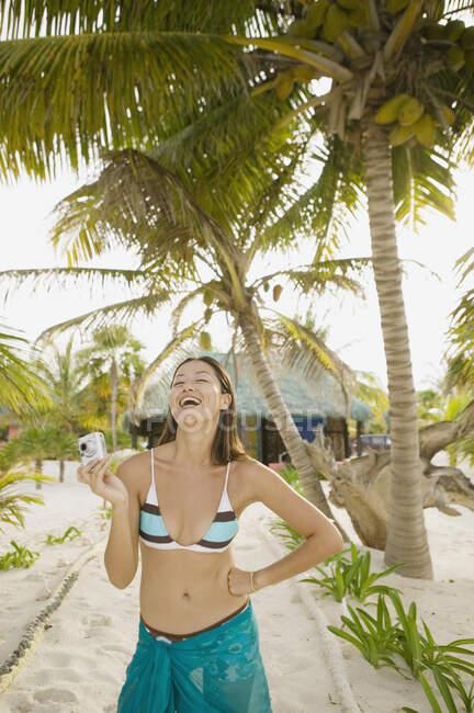 Donna che ride mentre usa la sua macchina fotografica digitale sulla spiaggia — Foto stock