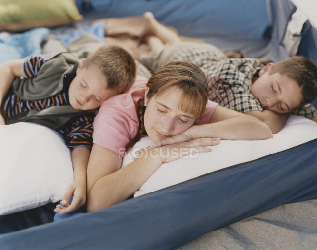 Mother and her two young sons resting in camping tent on beach — Stock Photo
