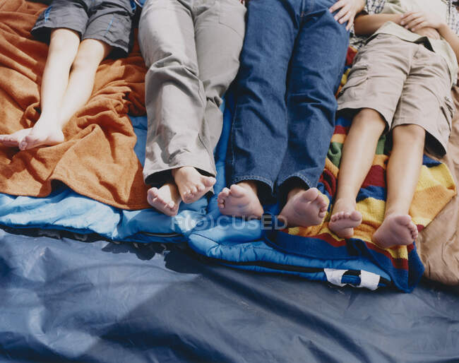 Family of four people lying on sleeping bags in a tent, waist down — Stock Photo