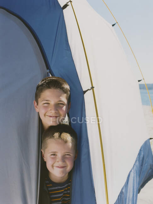 Two young brothers peeking out from inside camping tent — Stock Photo