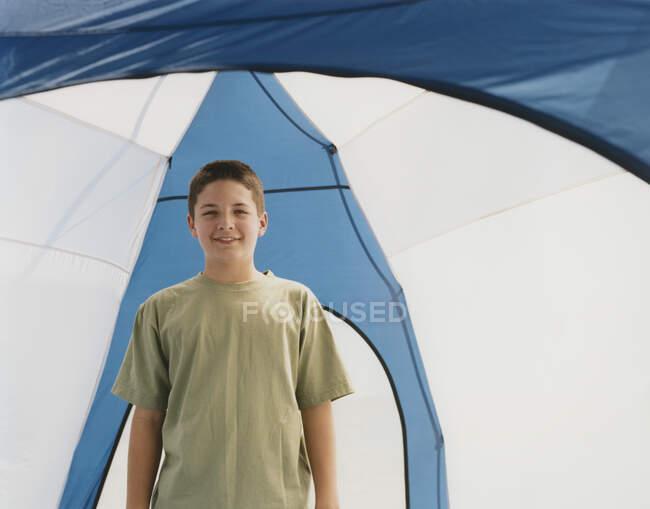 Щасливий юнак, що стоїть прямо в наметі в куполі. — стокове фото