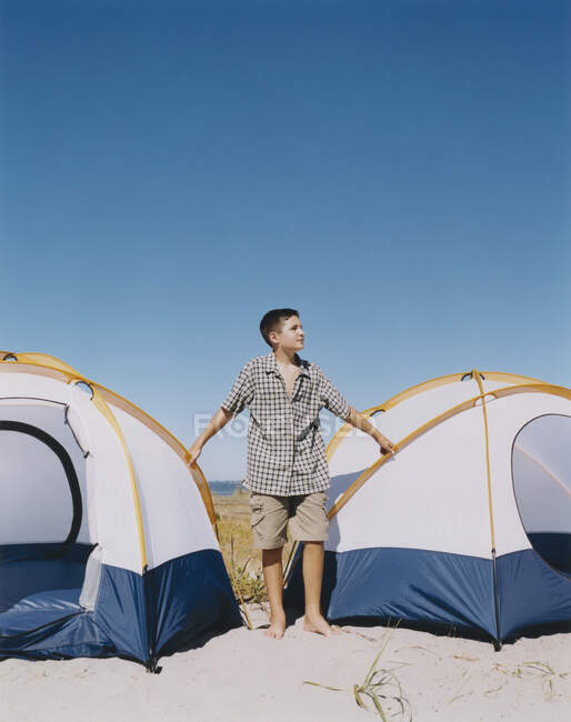 Adolescente de pé junto a tendas de acampamento na praia — Fotografia de Stock