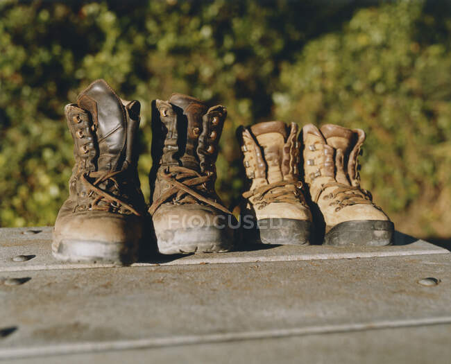 Dois pares de botas de caminhada de couro desgastado na mesa de piquenique — Fotografia de Stock