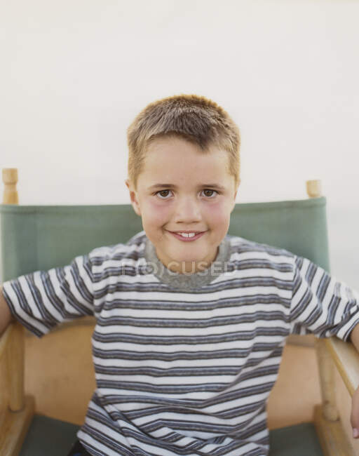 A confident boy sitting in a folding chair, smiling a toothy smile. — Stock Photo