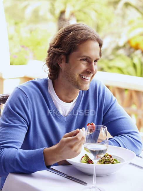 Glamorous Caucasian man eating in restaurant — Stock Photo