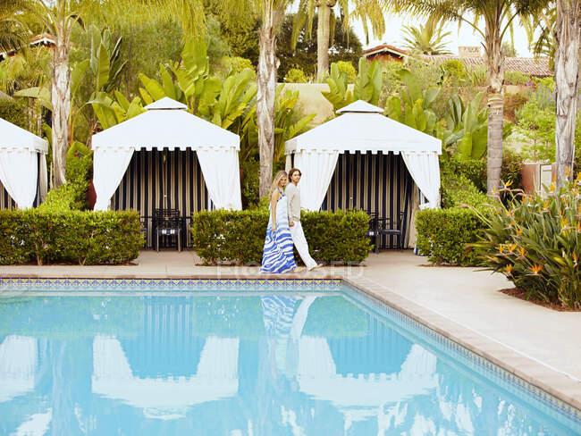 Coppia caucasica a piedi a bordo piscina — Foto stock