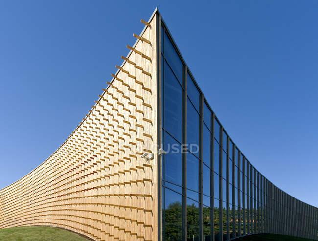Сучасні університетські будівлі, дерев'яні балки, що проектуються з вигнутої дерев'яної огорожі на вигнутій поверхні землі. — стокове фото